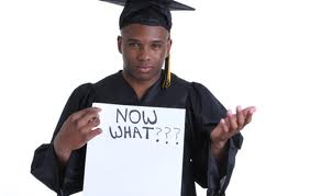 "a student in graduation gown and hat with a sign that reads. ""now what""."