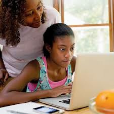 mother and child with homework on laptop