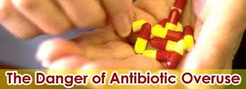 Left hand holding a bunch of yellow and red antibiotic medications, right hand pick up a pill