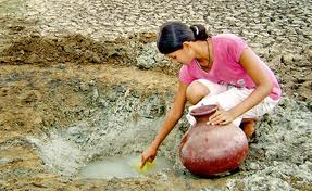 Young woman collecting water from a whole in the ground