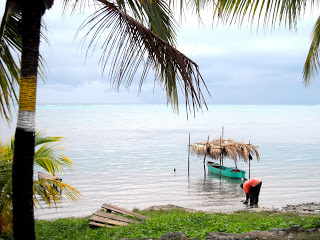 A fisheman dending down on the beach cleaning his catch as his canoe sits montionles on the calm waters of  roatan with a tach roof protecting it from the Sun  and rain.
