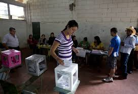 Young voman placing her vote in the balot box in Honduras